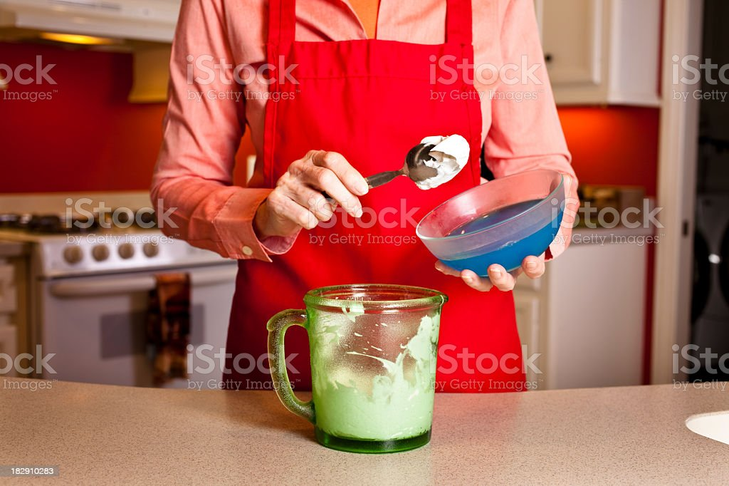 Senior woman in kitchen making whipping cream. stock photo
