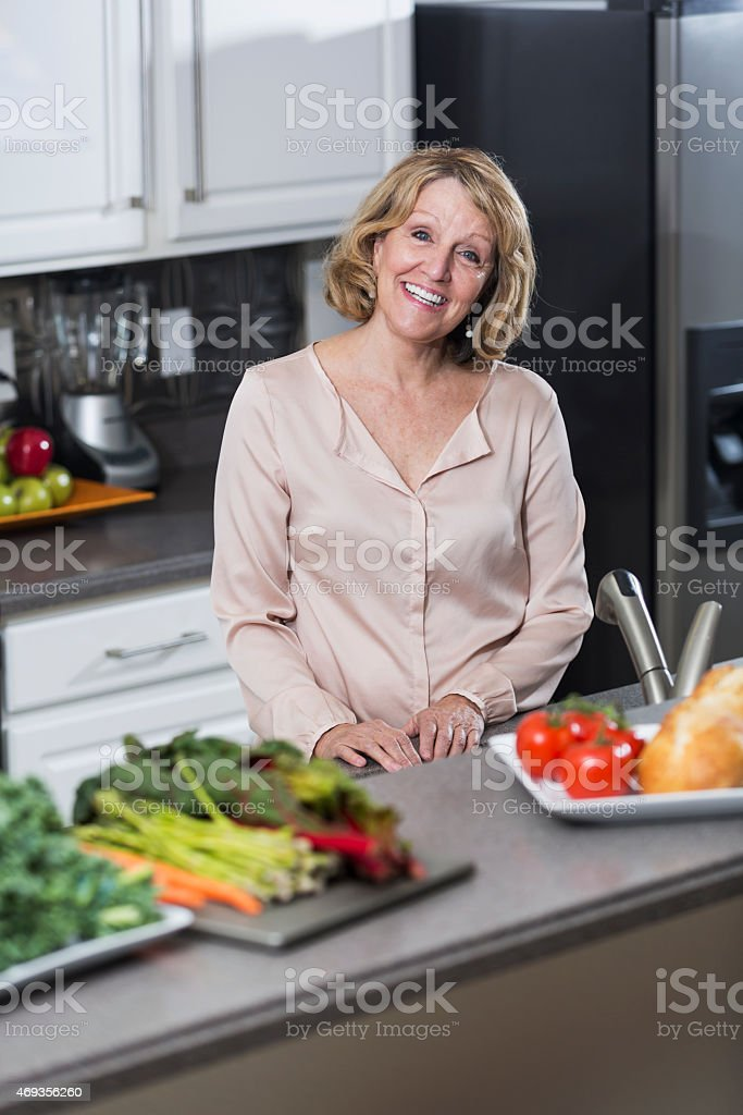 Senior woman in kitchen, vegetables on counter stock photo