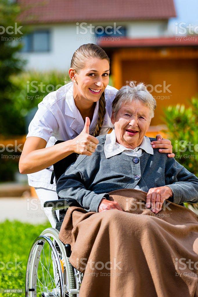 Senior woman in nursing home with nurse in garden sitting in...