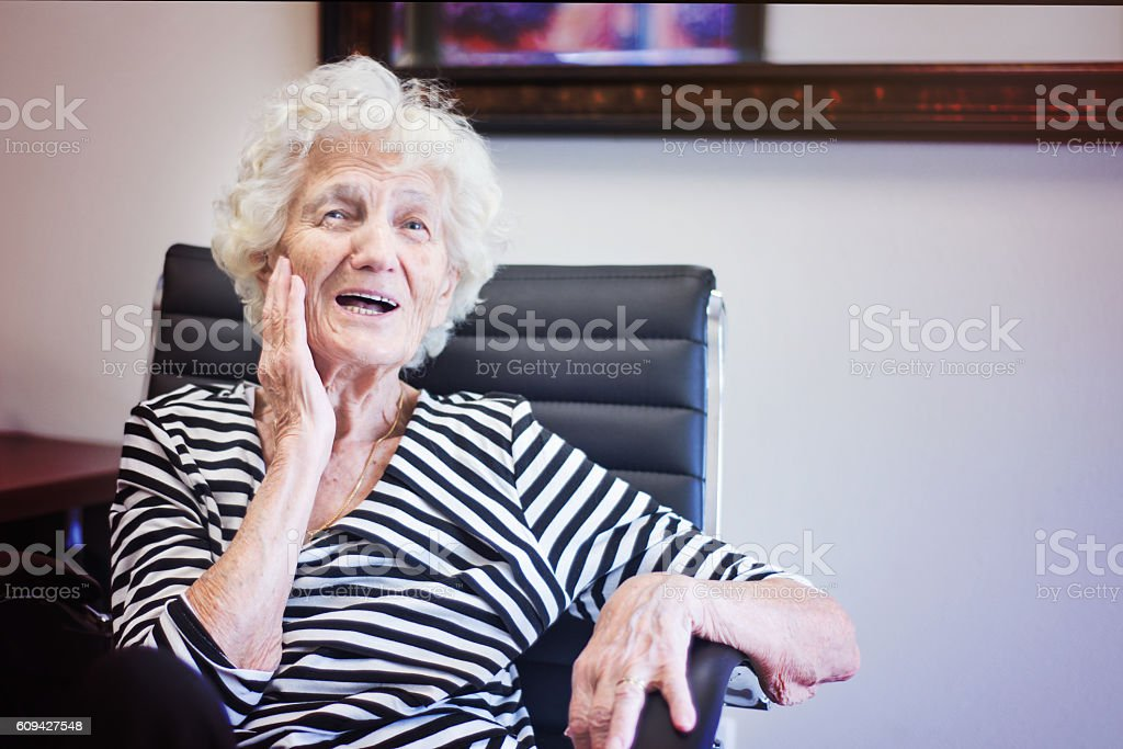 Senior Woman in Office Chair, Smiling stock photo