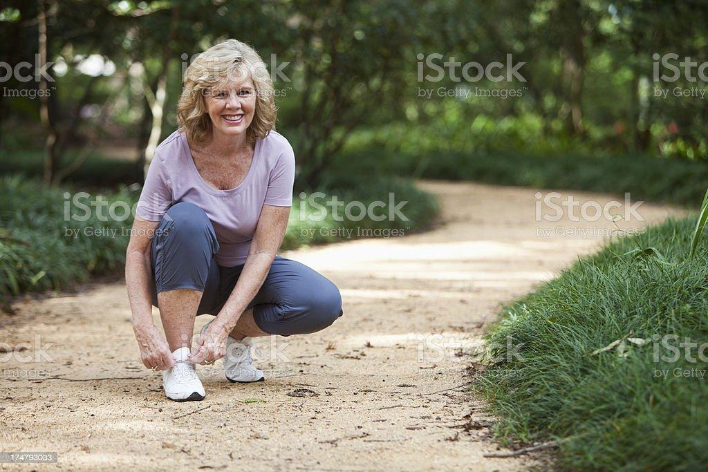 Senior woman in park, tying shoelace stock photo