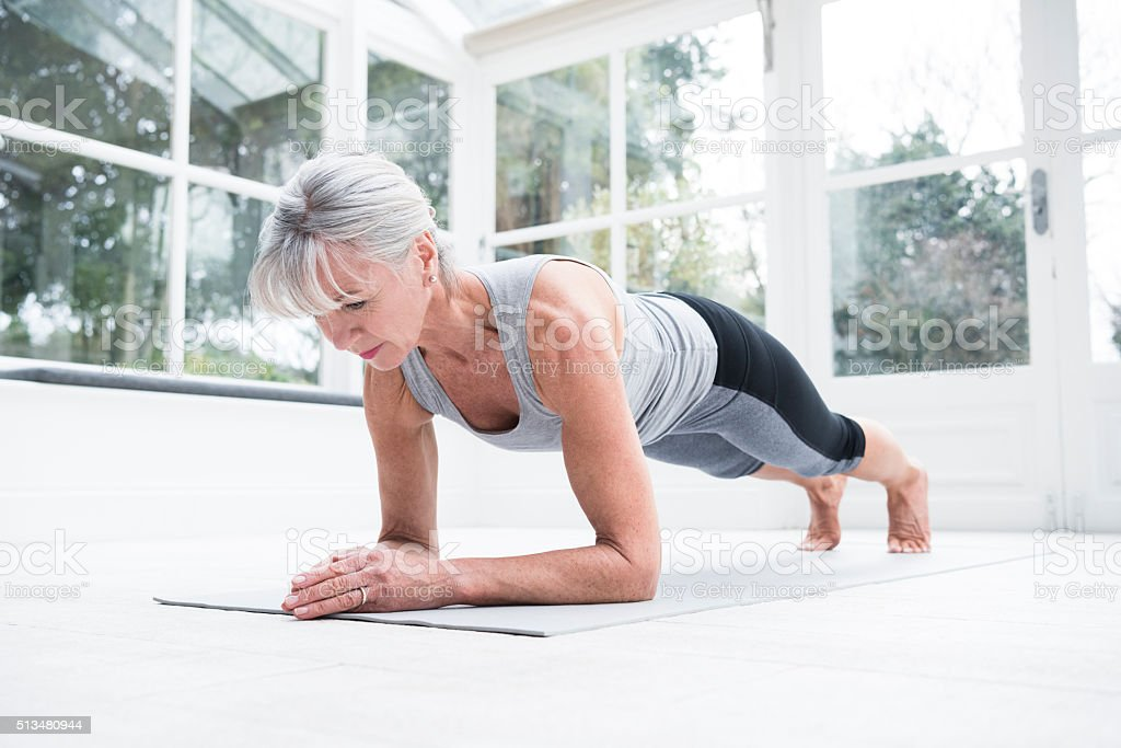 Senior woman in plank position in conservatory stock photo