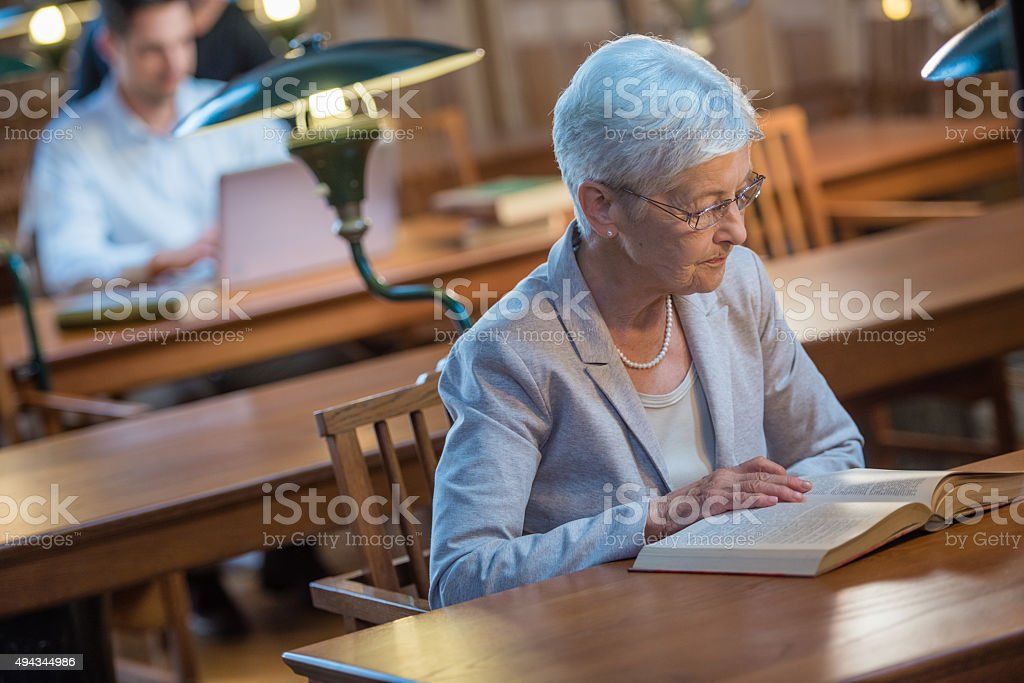 Senior woman in public library stock photo