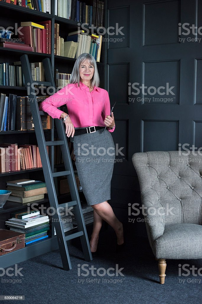 Senior woman in room with bookcases holding tablet stock photo