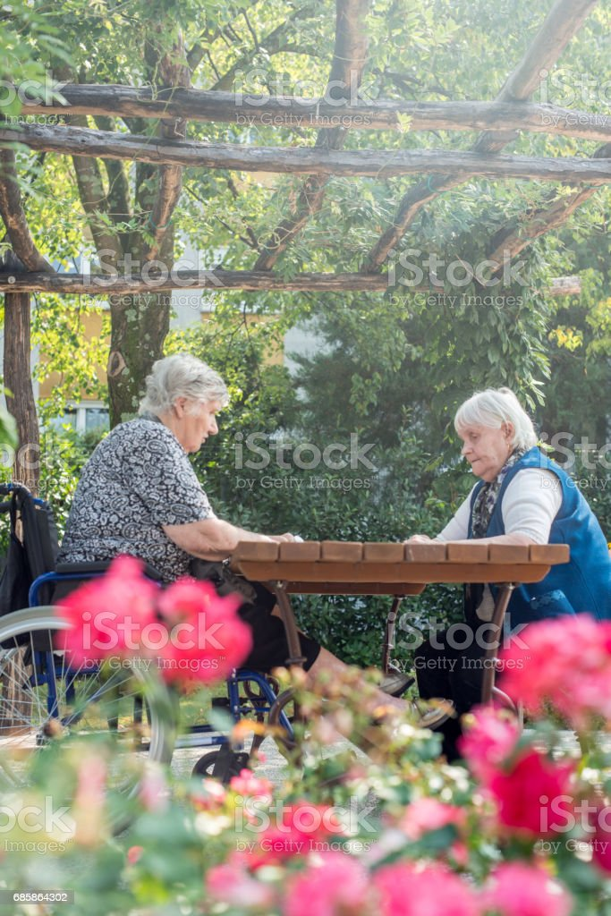 Senior Woman In The Nursing Home Playing Muehle Game Board For Relaxation stock photo