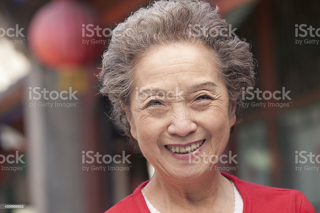 Senior Woman in Traditional Chinese Courtyard stock photo