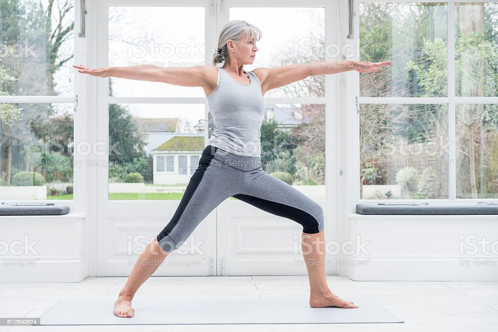 Senior woman in warrior yoga position with arms outstreteched stock photo