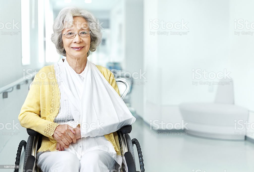 Senior woman in wheelchair and arm sling stock photo