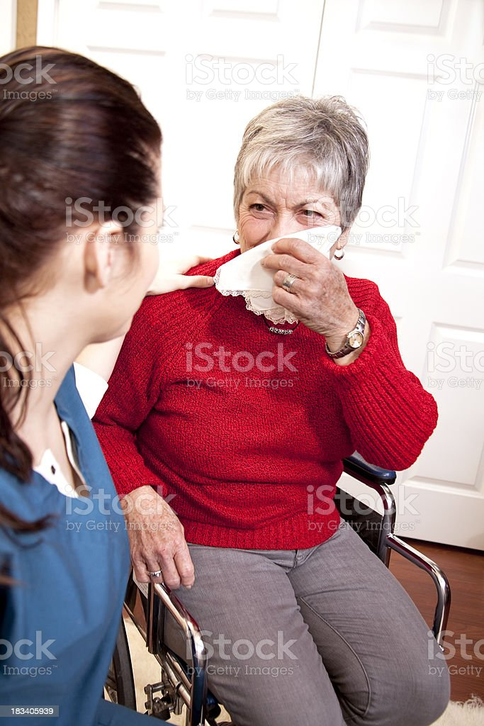 Senior woman in wheelchair being comforted by nurse royalty-free stock photo