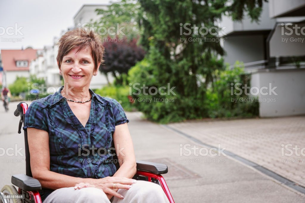 Senior woman in wheelchair, enjoying a day in the city stock photo