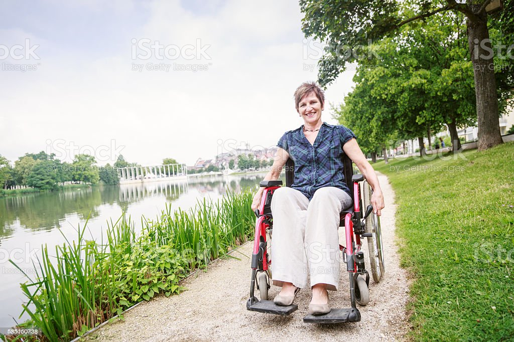 Senior woman in wheelchair, enjoying a day in the park stock photo
