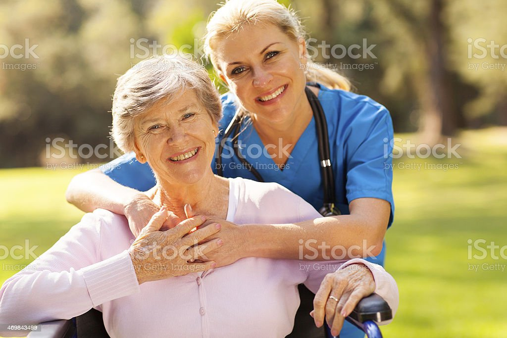 senior woman in wheelchair outdoors with caring caregiver stock photo