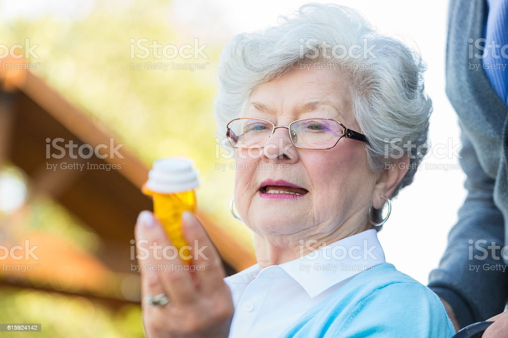 Senior woman in wheelchair reads prescription medication label stock photo