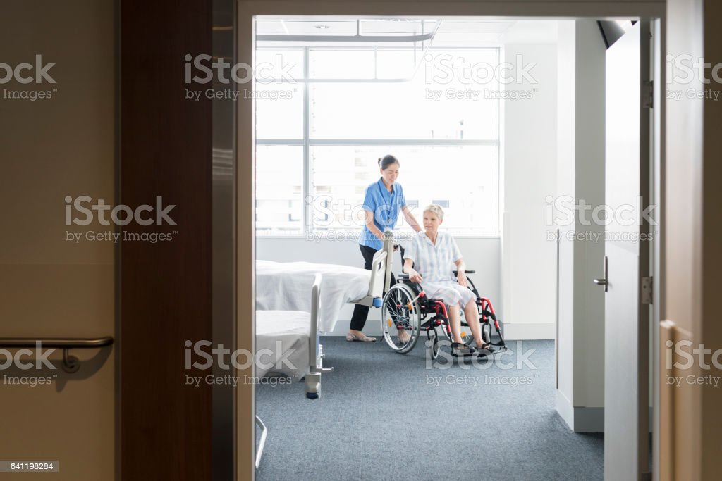Senior woman in wheelchair with female nurse on the ward stock photo
