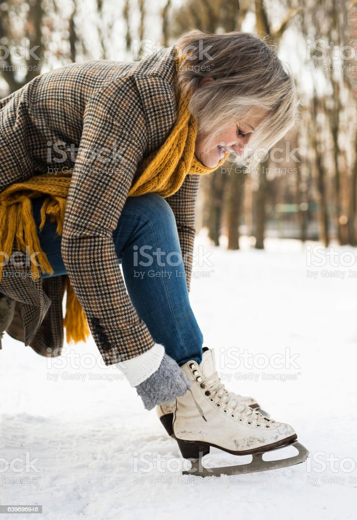 Senior woman in winter clothes putting on old ice skates. stock photo
