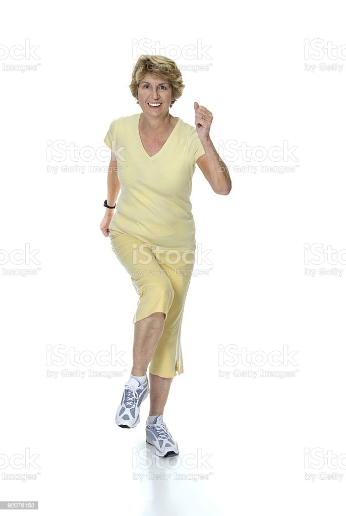 Senior woman in yellow suit running isolated royalty-free stock photo
