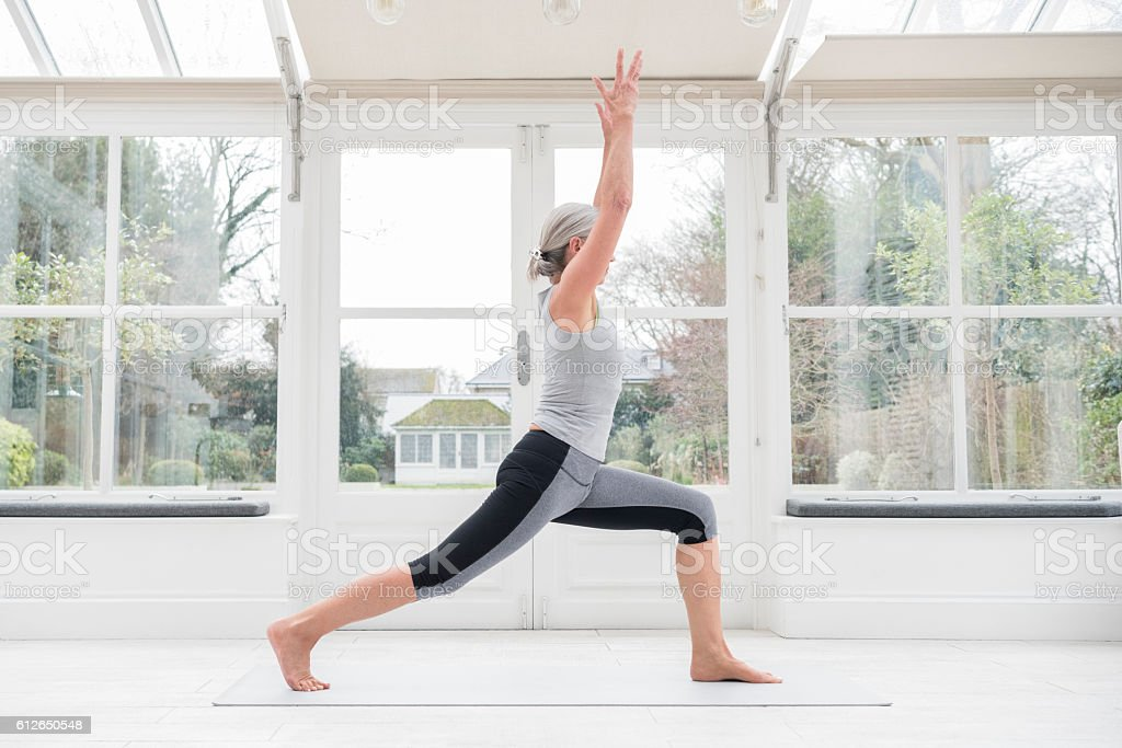 Senior woman in yoga post with arms raised stock photo