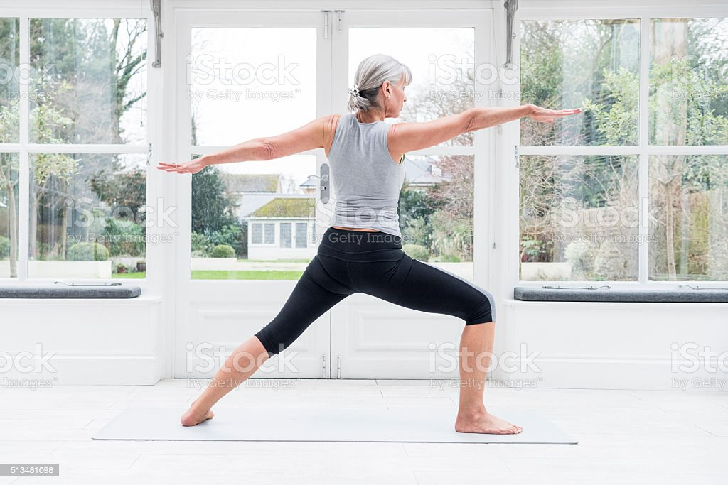Senior woman in yoga warrior pose with arms outstretched stock photo