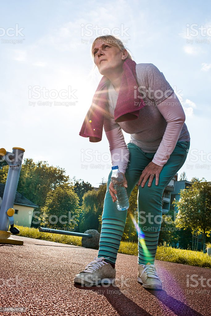 Senior woman injured herself during a sports training outdoors. stock photo