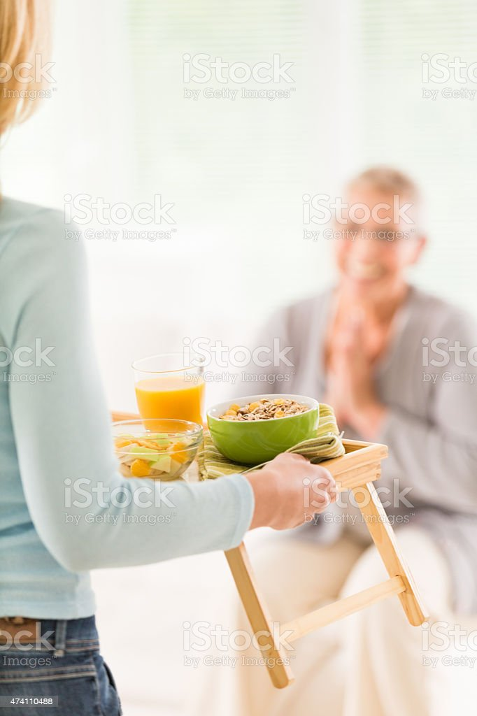 Senior woman is being served healthy breakfast stock photo