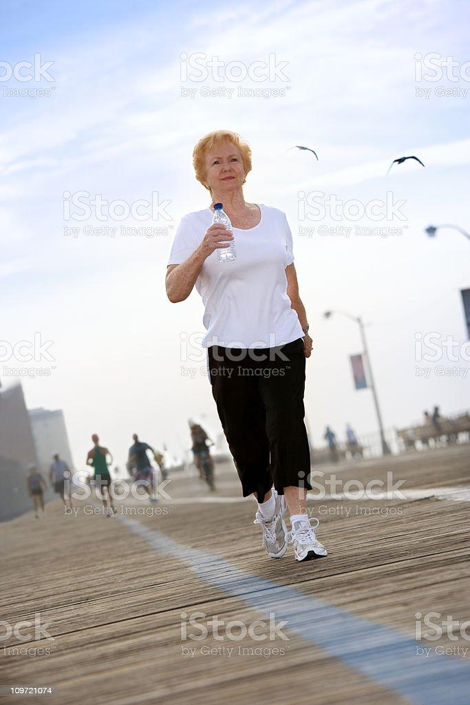 A senior woman is power walking on the boardwalk. royalty-free stock photo