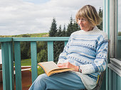 Senior woman is reading at a balcony