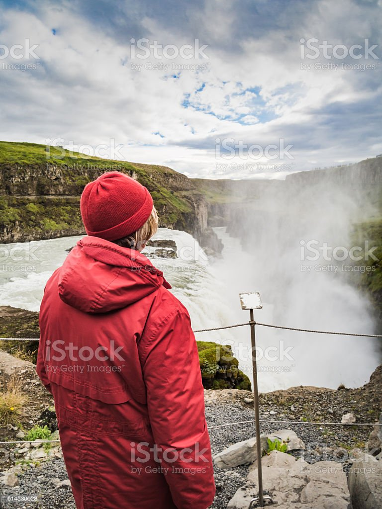 Senior woman is standing at a Gullfoss waterfall - Iceland stock photo
