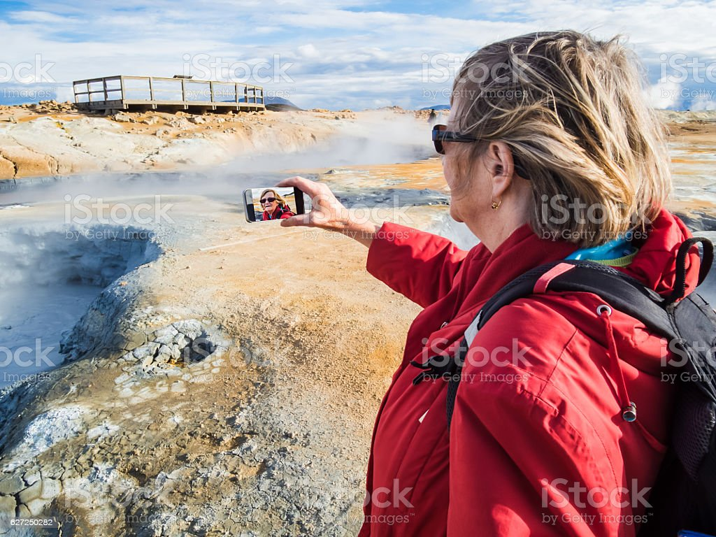 Senior woman is taking a selfie at a boiling mud stock photo