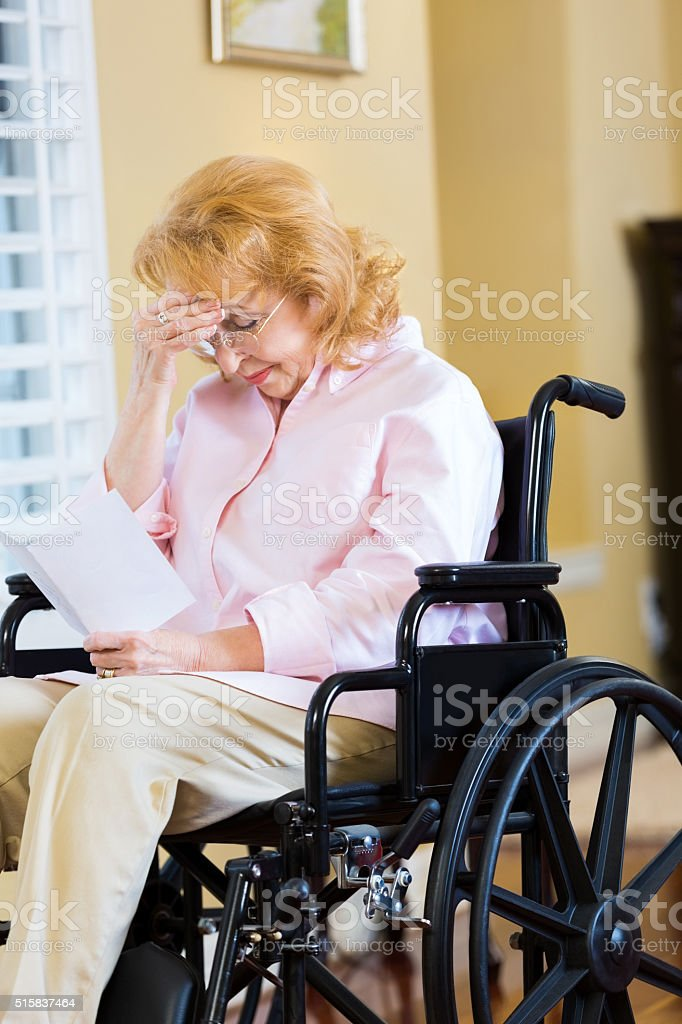 Senior woman is upset as she reads card stock photo