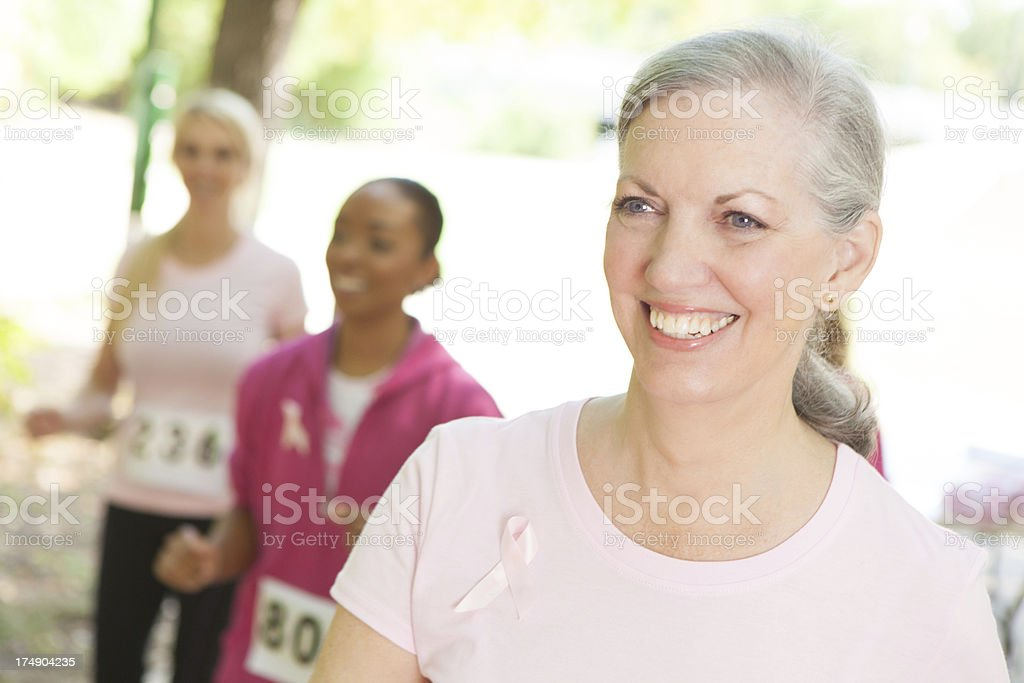 senior woman jogging with pink ribbon royalty-free stock photo