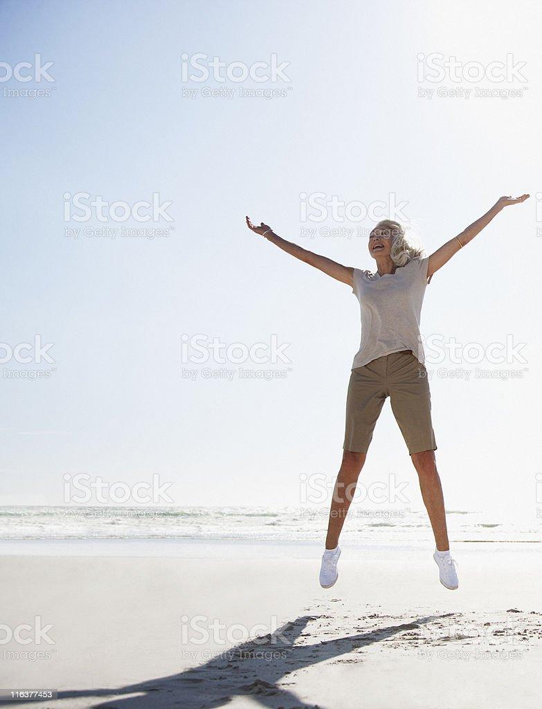 Senior woman jumping on beach stock photo