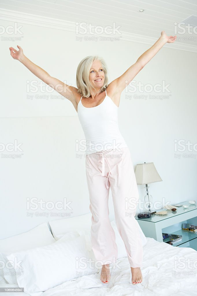 Senior Woman Jumping on Bed stock photo