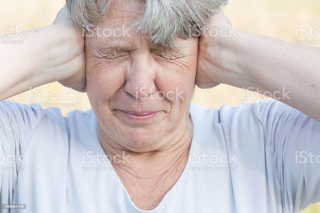 Senior woman keeps her ears shut stock photo