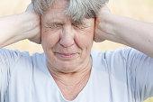 Senior woman keeps her ears shut