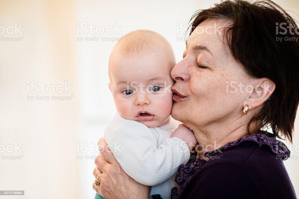 Senior woman kisses her grandchild stock photo