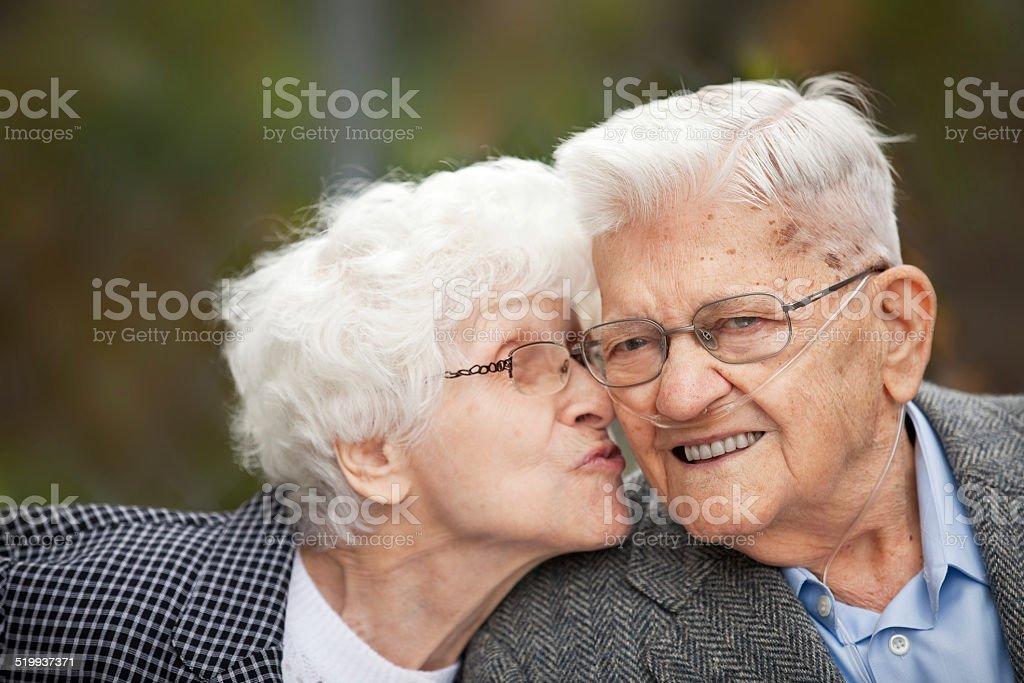 Senior Woman Kissing Her Husband stock photo