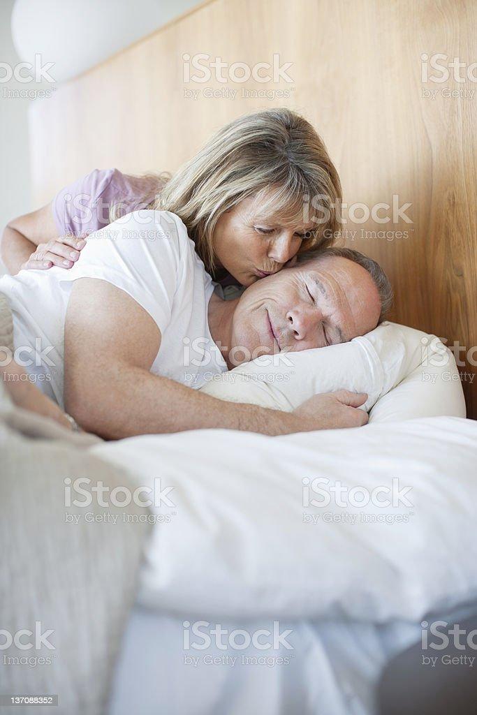 Senior woman kissing man asleep in bed royalty-free stock photo