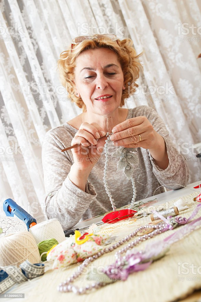 Senior woman knitting jewelry stock photo