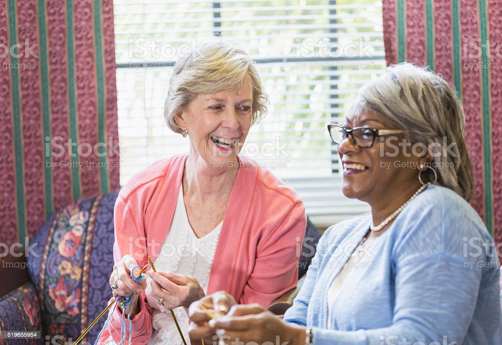 Senior woman knitting with African American friend stock photo