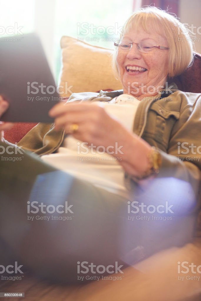 senior woman laughing as she uses digital tablet stock photo
