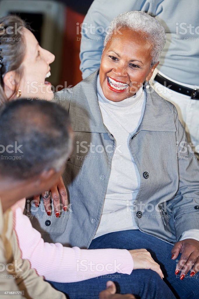 Senior woman laughing with friends stock photo