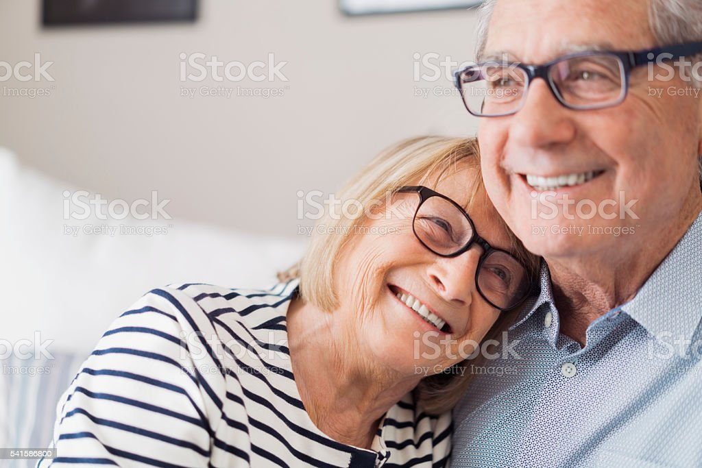 Senior woman leaning head on senior man's shoulder stock photo