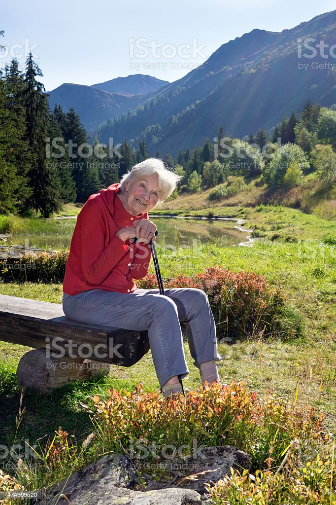 Senior woman leaning on walking steak in the mountains. stock photo
