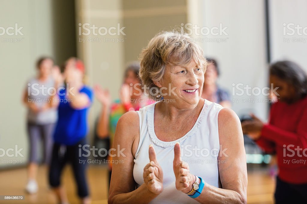 Senior woman learning dance move at senior center stock photo