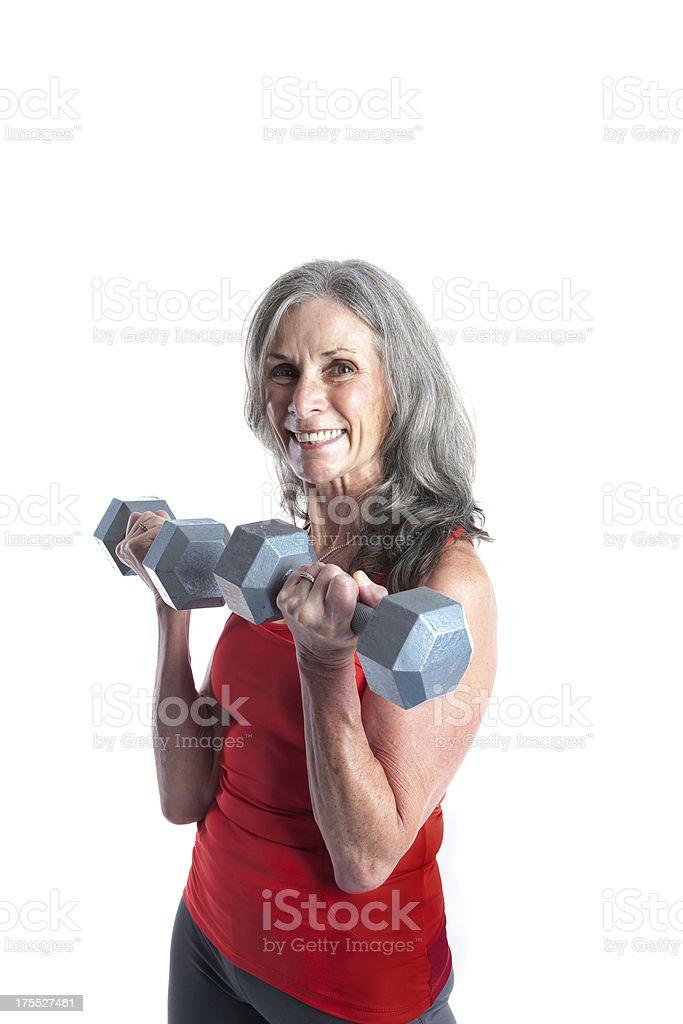 Senior woman lifting Dumbbells against white background royalty-free stock photo