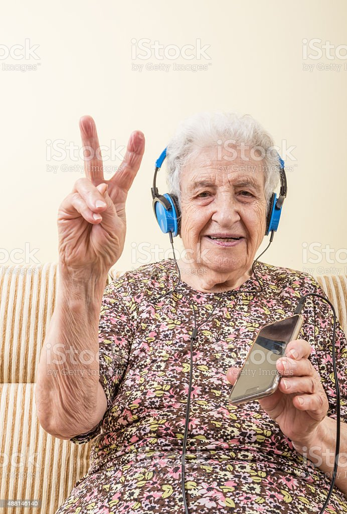 senior woman listening music  with headphones stock photo
