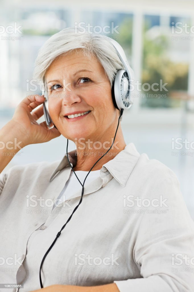 Senior woman listening to music royalty-free stock photo