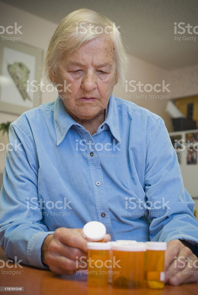 Senior woman looking a pill bottles royalty-free stock photo