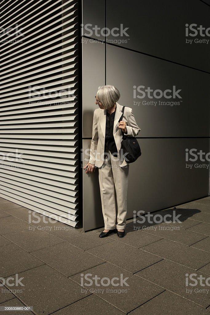 Senior woman looking around corner on street at night stock photo
