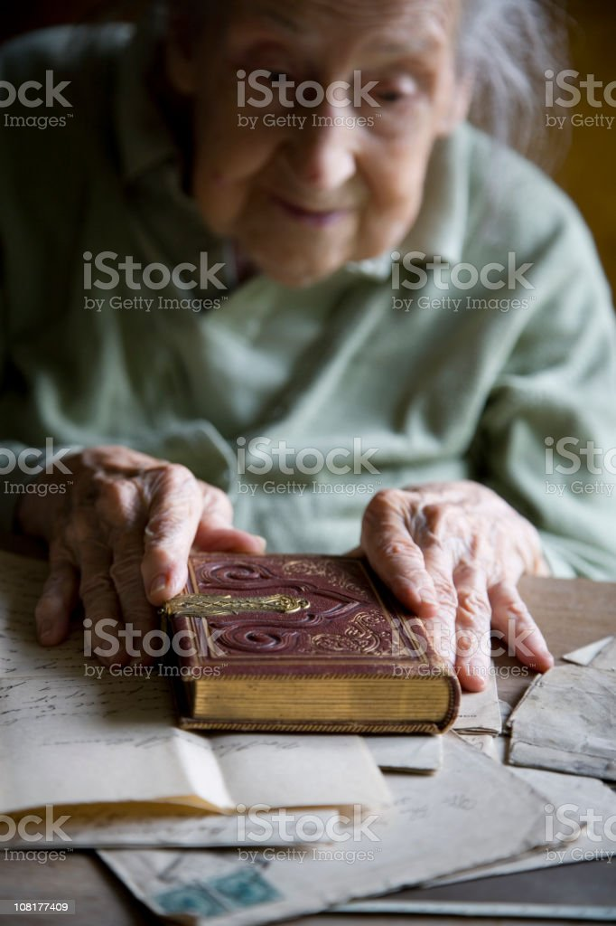 Senior Woman Looking at Antique Book and Old Letters royalty-free stock photo